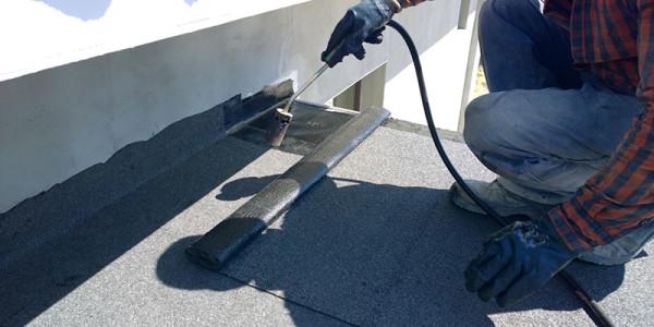 Roofer preparing part of bitumen roofing felt roll for melting b